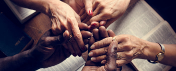 Closeup of four people holding hands over bibles