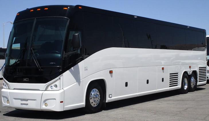 a plain white MCI charter bus parked on pavement